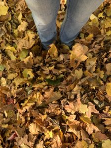 Lower half of a person standing in a pile of autumn leaves. Their shoes are totally covered with leaves.