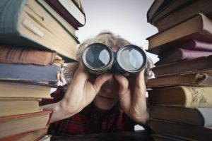 Man using binoculars while sitting between two stacks of thick, dusty books at a large wooden table