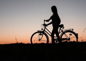 Silhoutte of person pushing an upright bicycle on a hill at dusk