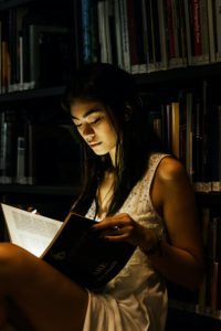 Woman reading a book in a dark library. There is a bright light emanating from the book.