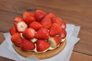 A strawberry tart with whole, fresh strawberries piled on top of it.