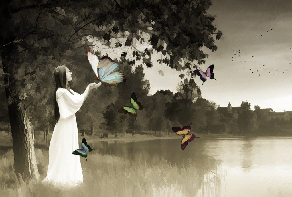 stylized black and white drawing of woman in white dress touching butterflies the size of large owls. the blue, green, orange, and pink butterflies are the only splashes of colour in this scene.