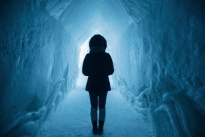 Person standing in a 6+ foot tall tunnel built into thick walls of snow and ice.