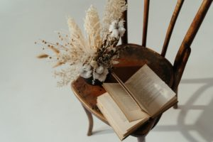 a book and a dried bundle of flowers sitting on a wooden chair