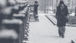 black and white photo of person walking alone on a city sidewalk during a snowstorm