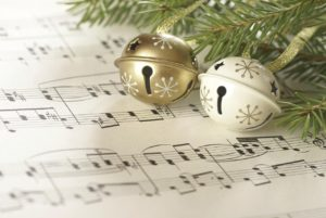 christmas bells hanging from a christmas tree over a sheet of music.
