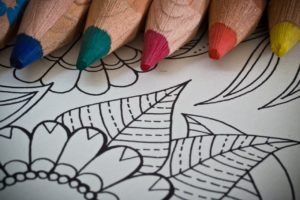 close-up photo of a colouring book for adults with coloured pencing resting on one of its opened pages