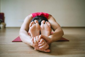 woman doing yoga. stretching head down into lap.