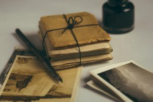 A fountain pen lying next to old black and white photographs and a bundle of documents wrapped in brown paper and tied up with black string