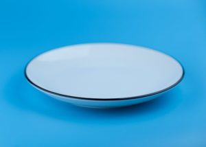 An empty white plate on a blue background