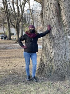 A petite woman bundled up for winter and standing next to a large tree