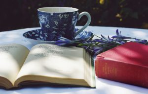 book opened on top of white table beside closed red book and run blue foliage ceramic cup on top of saucer