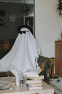 person wearing a white sheet over their body and sitting on a couch. they are also wearing sunglasses and a hat.