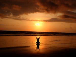 silhoutte of person sitting by a beach and raising their hands to the sky as the sun sets