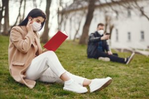 two people wearing masks, social distancing, and reading books outside at a park.