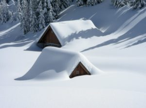 two wooden cottages almost totally covered in snow