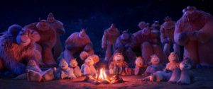 A large group of yetis gathered around a fire listening to stories.