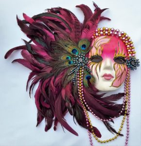 A pink mardi gras mask with purple, blue, and yellow feathers sticking out of it.