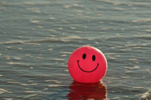 A red ball with a smiley face on it. The ball is floating in a large body of water.