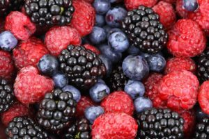 close-up photo of fresh raspberries, blackberries, and blueberries