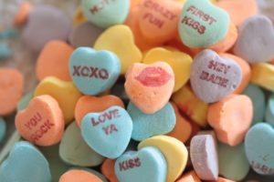 conversation heart candies. The messages printed on them include kiss, you rock, xoxo, hey babe, and a drawing of a pair of lips pursed up to kiss someone.
