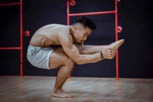flexible young asian man doing balancing asana during hatha yoga training