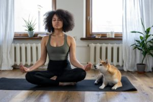 woman meditating while her dog looks on