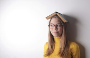 woman wearing a book on her head and smiling slightly.