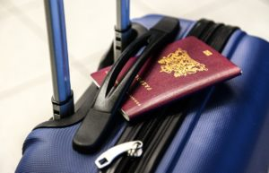 A red passport tucked into the handle of a blue wheeled suitcase