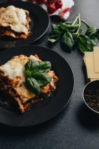 Lasagna on black plate with a sprig of a green plant on the food.