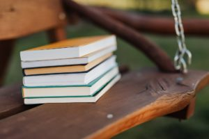 Stack of books on a wooden swing.