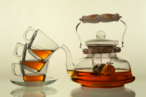 Three clear glass teacups stacked on top of each other. Each one contains a small amount of tea, and they're sitting next to a clear glass teapot that is half full of tea.