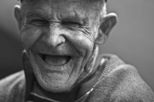 black and white photo of an elderly man who is laughing.