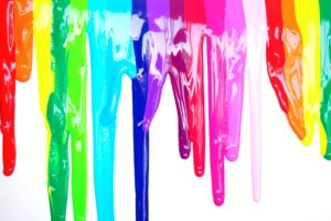 Multicolored paint dripping down a white background