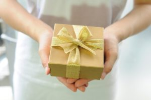 Woman holding a gift wrapped in gold paper and a gold ribbon