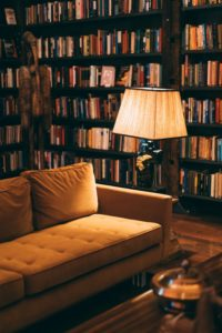 A lamp turned on next to a soft couch in a library whose walls are lined with books