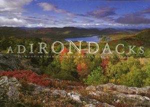Adirondacks- Views of An American Wilderness by Carl E. Heilman II book cover. Image on cover is panoramic shot from a mountaintop to the lush forest and lake below.