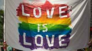 """White piece of cloth that has a rainbow and the phrase """"love is love"""" painted on it."""