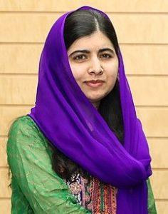 Photo of Malala Yousafzai wearing a green dress and a purple headscarf