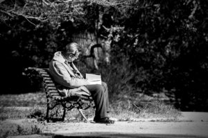 black and white photo of slumped over man reading a book while sitting on a park bench outdoors