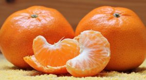peeled tangerine next to two whole tangerines