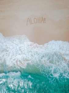 Arial shot of waves gently lapping against a large sandy beach. Someone has scratched the world aloha into the sand.