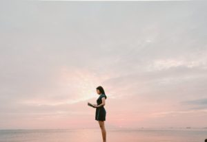 Woman standing on a beach at sunset reading a book. There is a beautiful pink sky behind her.