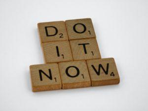 "Scrabble blocks spelling out ""do it now."""