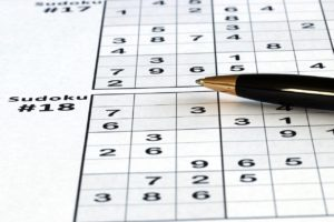 Close-up photo of a ballpoint pen lying on a sheet of Sudoku puzzles