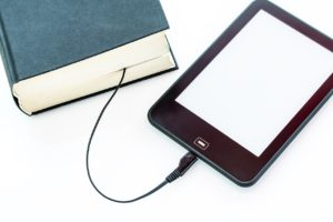 An ereader with it's cord tucked between the pages of a hardcover book.