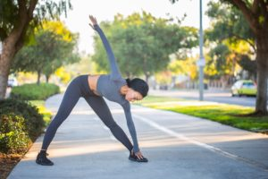 Woman bent over at the waist and touching her toes. She's stretching before a run.